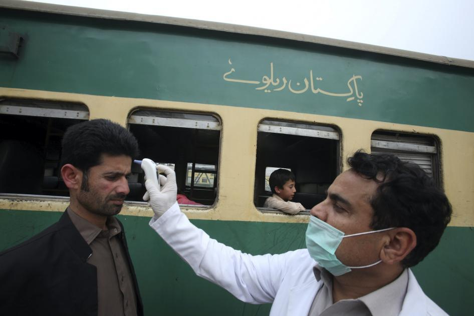 A Volunteer Checks the Temperature of Passengers Arriving at a Railway Station in Peshawar, AP Photo, 17 March 2020, (https://www.hrw.org/news/2020/03/19/pakistan-prisoners-risk-covid-19)