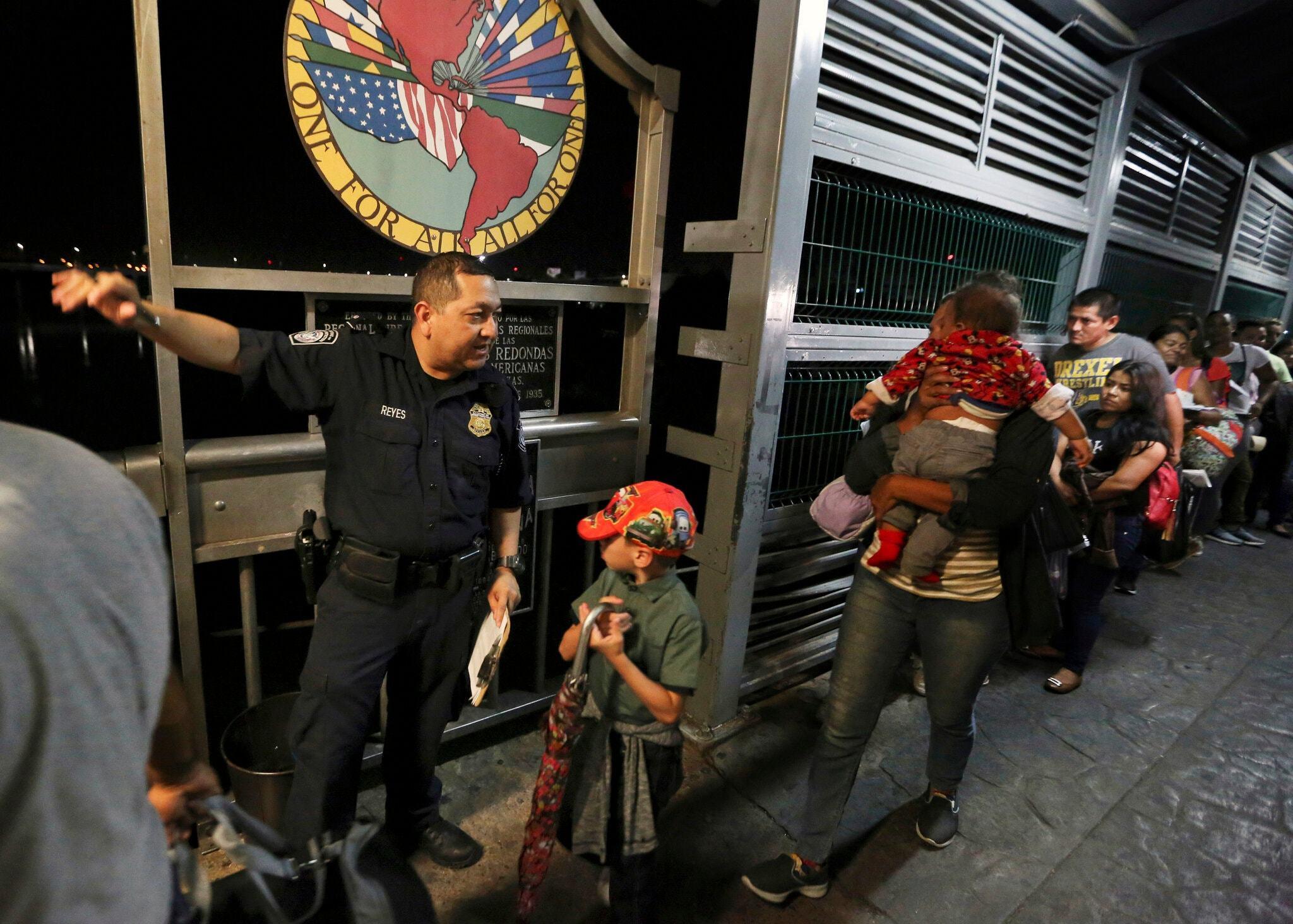 A U.S. Customs and Border Officer Guiding Asylum-Seeking Migrants Across a Bridge from Nuevo Laredo, Mexico, into the U.S., (Fernando Llano, Associated Press,