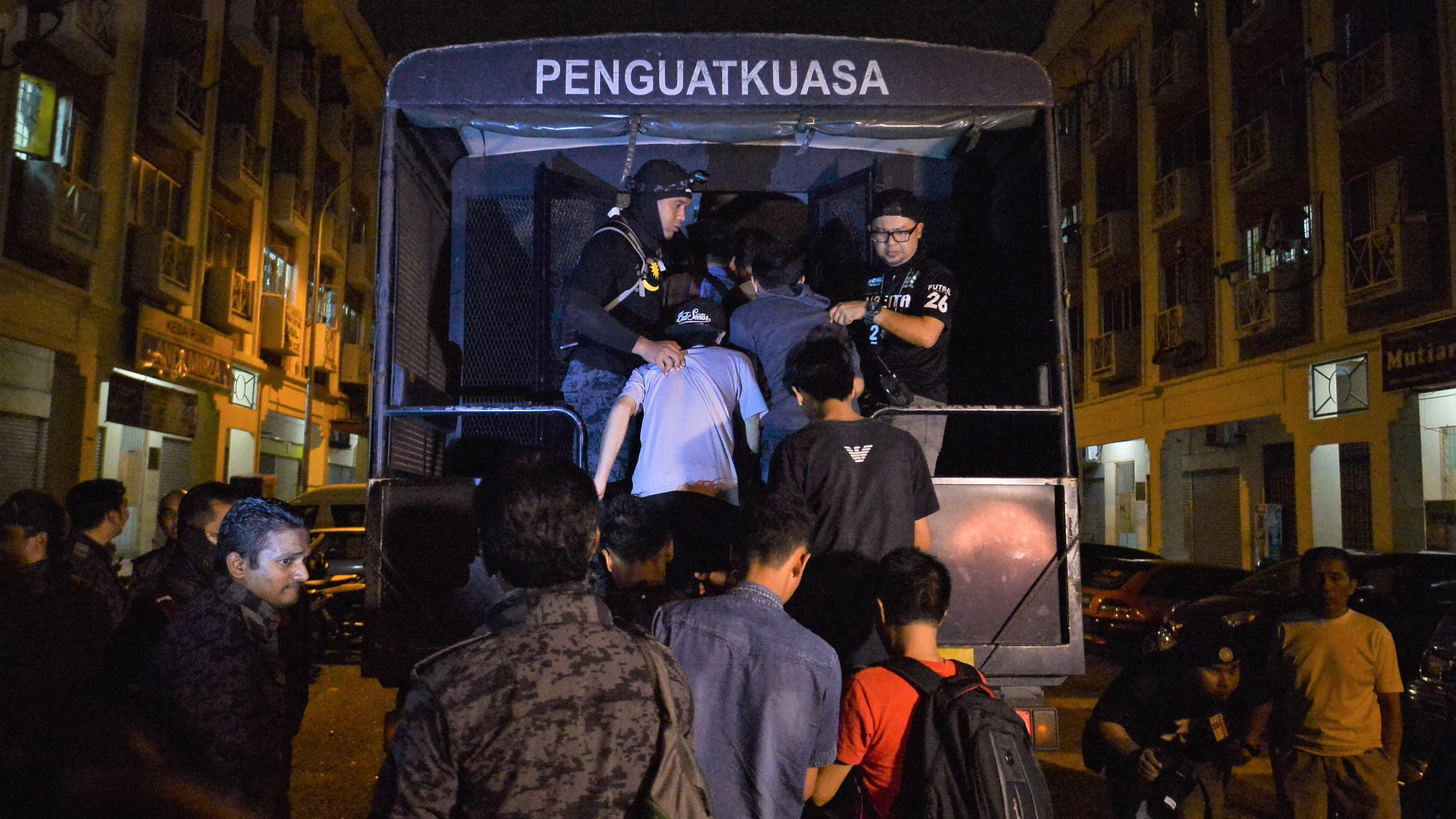Malaysian Immigration Officers usher Detainees into a Truck after a Raid in 2018, (Getty Images,