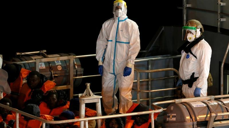Armed Forces of Malta in Protective Clothing Stand Near Rescued Migrants on a Military Vessel After it Arrived in Senglea in Valletta, After an Outbreak of the Coronavirus Disease, (Darrin Zammit, Lupi/Reuters,