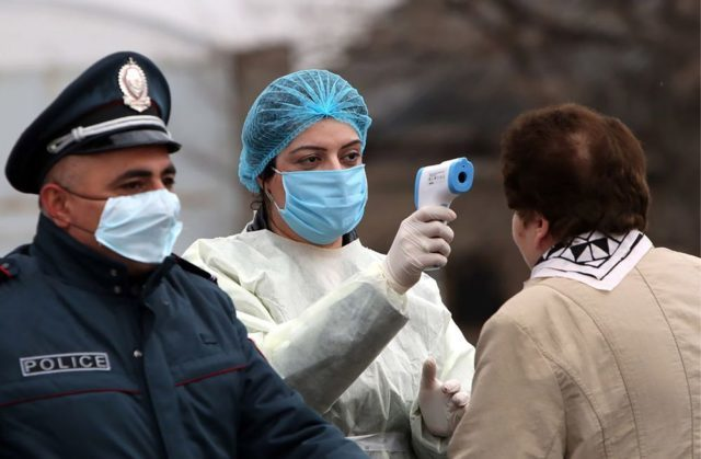 Police Officer Standing Next to a Health Worker Taking a Person's Temperature, (Bloomberg,