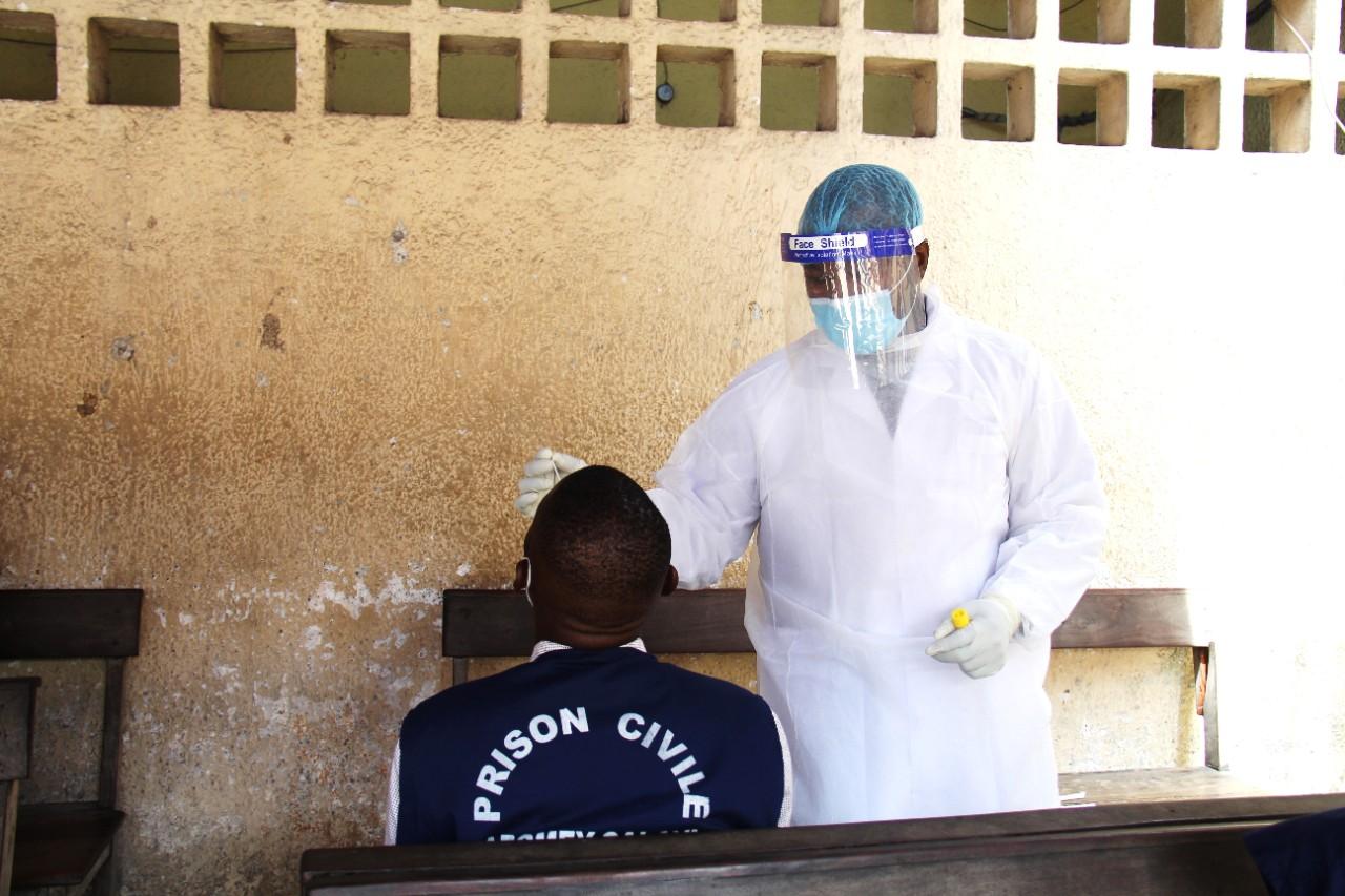 """Volunteer Doctor Testing a New Prisoner for COVID-19, (UNDP, """"Protéger les Droits des Détenus au Bénin,"""" 27 April 2021, https://tinyurl.com/4rfdjdv8)"""
