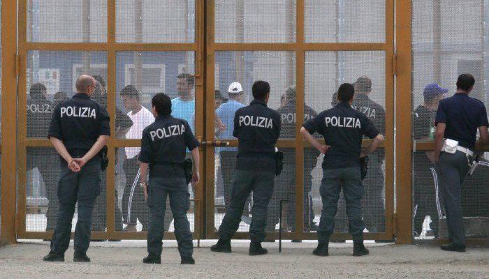 Police Officers Guarding Entrance to Immigration Detention Centre, (https://www.lasciatecientrare.it/emergenza-coronavirus-bloccare-gli-ingressi-nei-cpr-e-procedere-alla-progressiva-chiusura-dei-centri/)