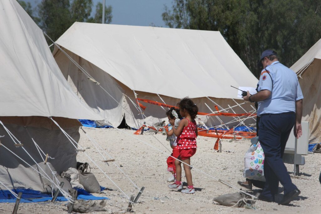 Two Children and an Official at the Pournara Migrant Camp, (Cyprus Mail,