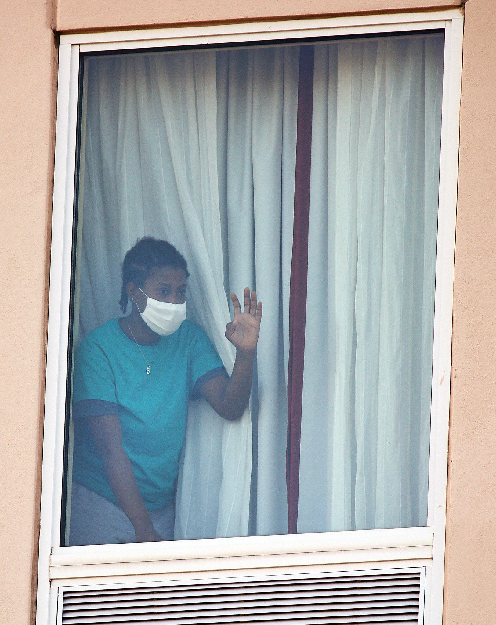 A Person Waves to Protesters Demonstrating Against the Practice of Detaining Migrants in Hotels at a Hampton Inn in McAllen in July, (Joel Martinez, The Monitor,