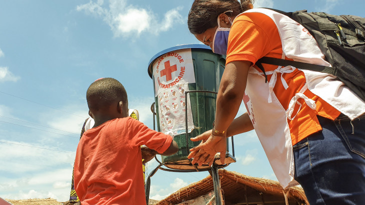 A Red Cross Volunteer in Bégoua Teaching a Child How To Properly Wash His Hands, (ICRC,