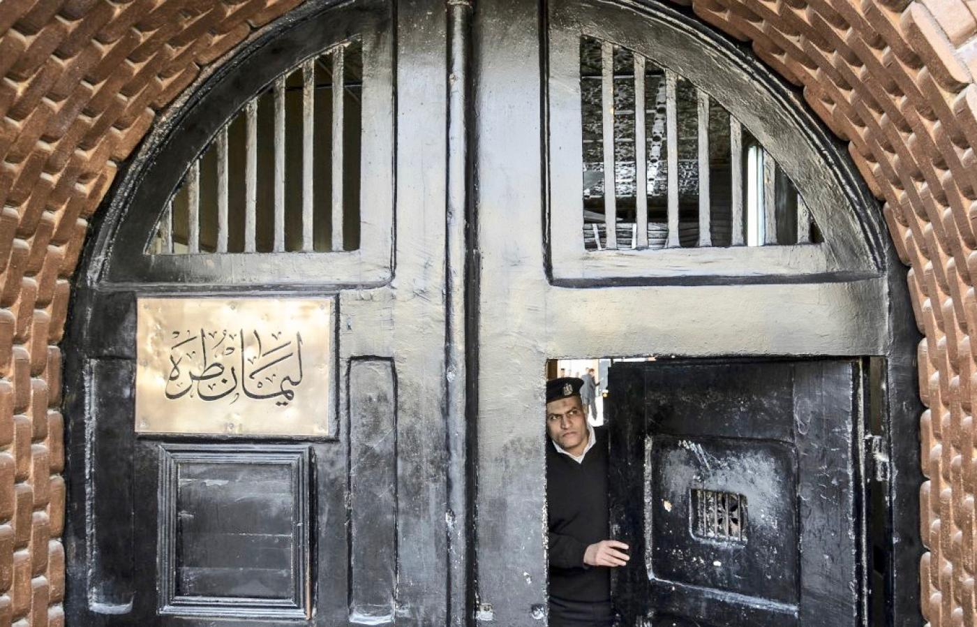An Egyptian police officer stands in the entrance to Tora Prison, Cairo (https://www.middleeasteye.net/news/coronavirus-egypt-prison-letter-smuggled-out-doctors-who-want-help-fight-pandemic)