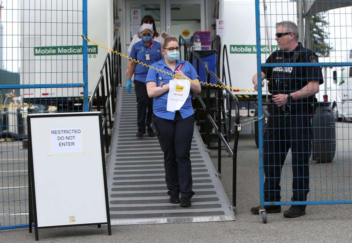 A Prison Guard Keeps Watch as Medical Workers Walk at a Secure Mobile Medical Unit Set-up at the Abbotsford Regional Hospital to Treat Prisoners with Covid-19, (Jesse Winter, Reuters,