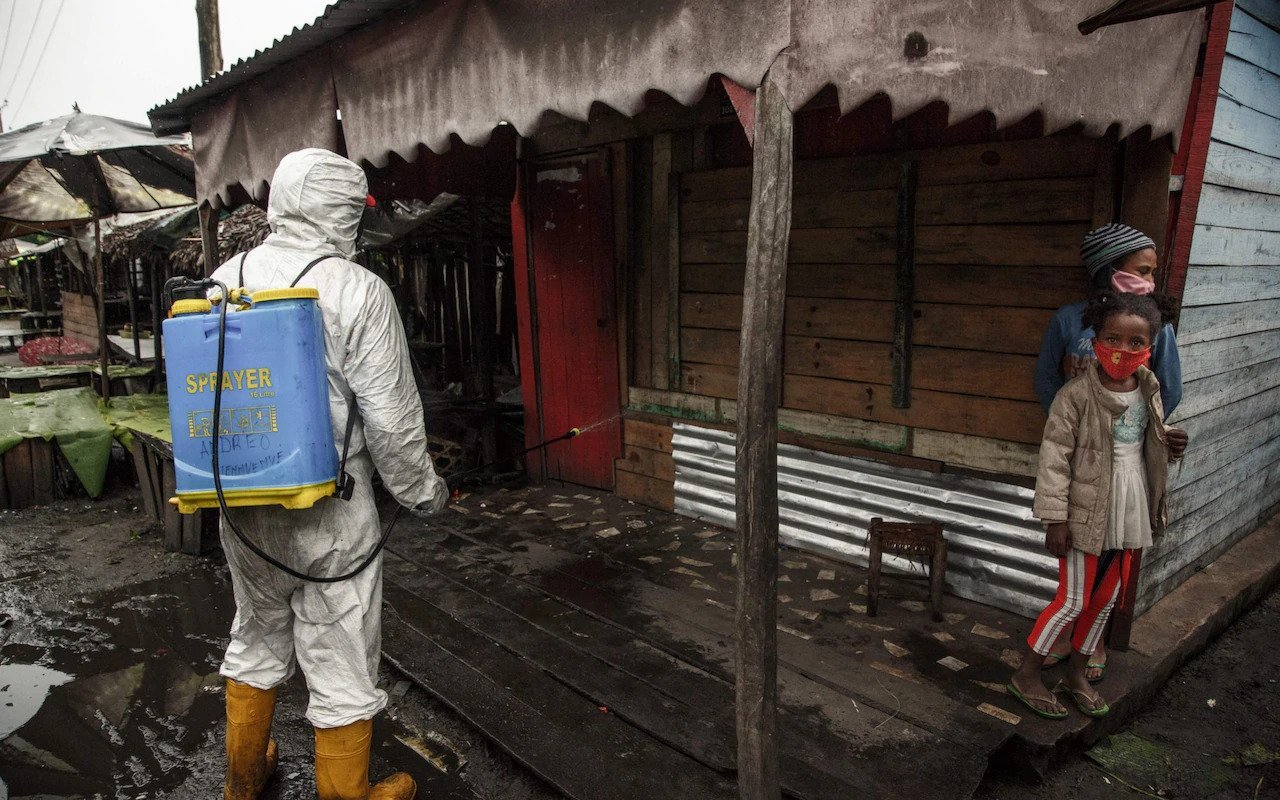 A Health Official Spraying a Shop Front in Toamasina in June 2020, (Rijasolo, AFP,