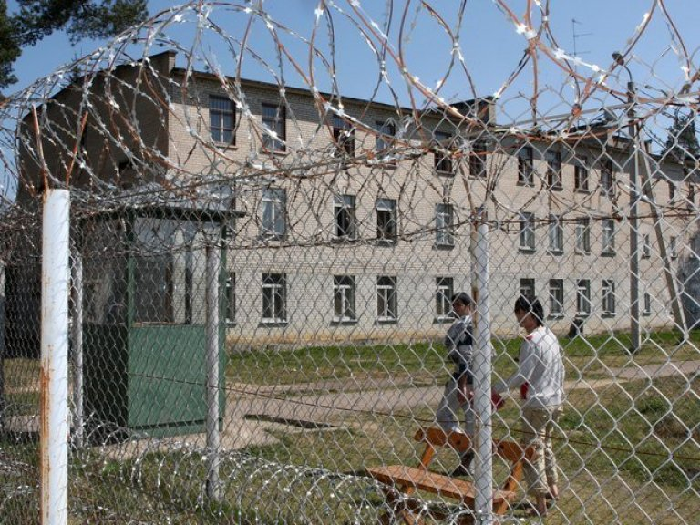 Two Detainees Seen Through Barbed Wire at Pabrade Detention Centre, (GB Times Lithuania,