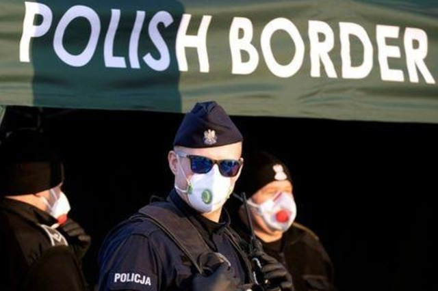 A Polish police officer stands at the country's border with Germany, symptoms testing drivers entering the country (https://uk.reuters.com/article/uk-health-coronavirus-poland-prisons/poland-to-let-more-prisoners-serve-sentences-at-home-amid-coronavirus-idUKKBN21A20C)