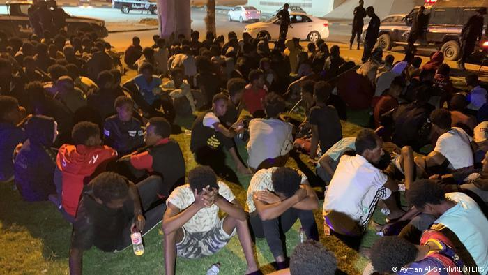 Migrants Sitting on the Street After Being Rounded Up by Security Forces (Ayman Al-Sahili, Reuters,