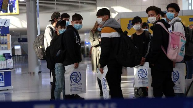 Relocated Unaccompanied Minors in Luxembourg Airport Holding IOM Bags, (Getty Images, BBC News,