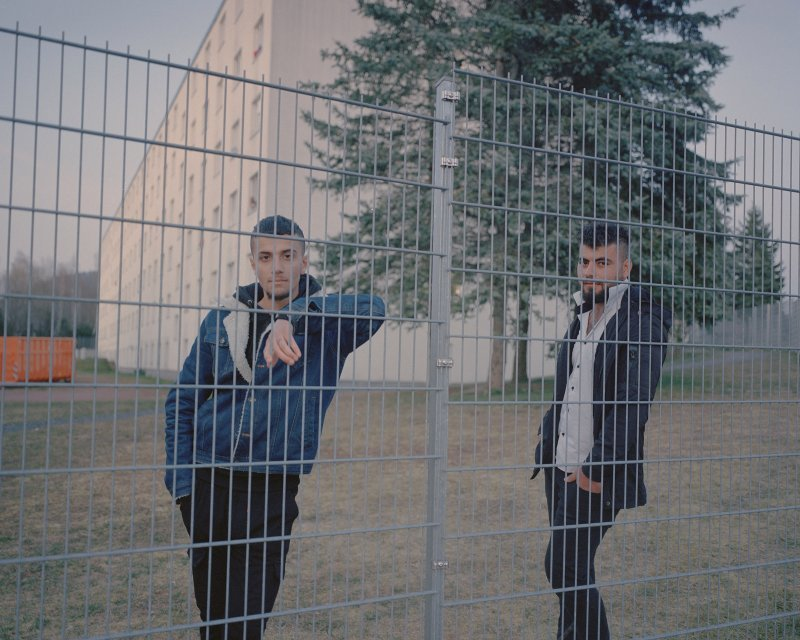 Two Refugees Standing at the Fence of the Suhl Refugee Reception Centre, (Ingmar Björn Nolting, DOCKS Collective,